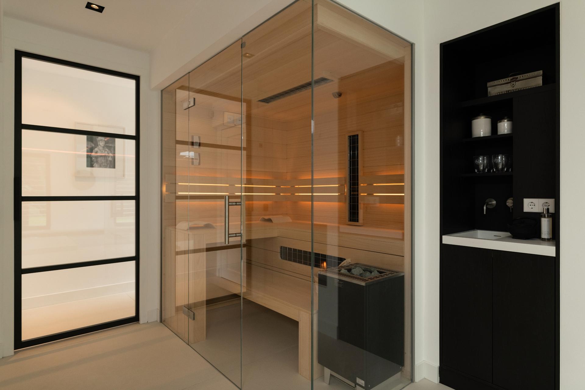 Sauna combinatie op maat met glaswand in moderne wellnessruimte