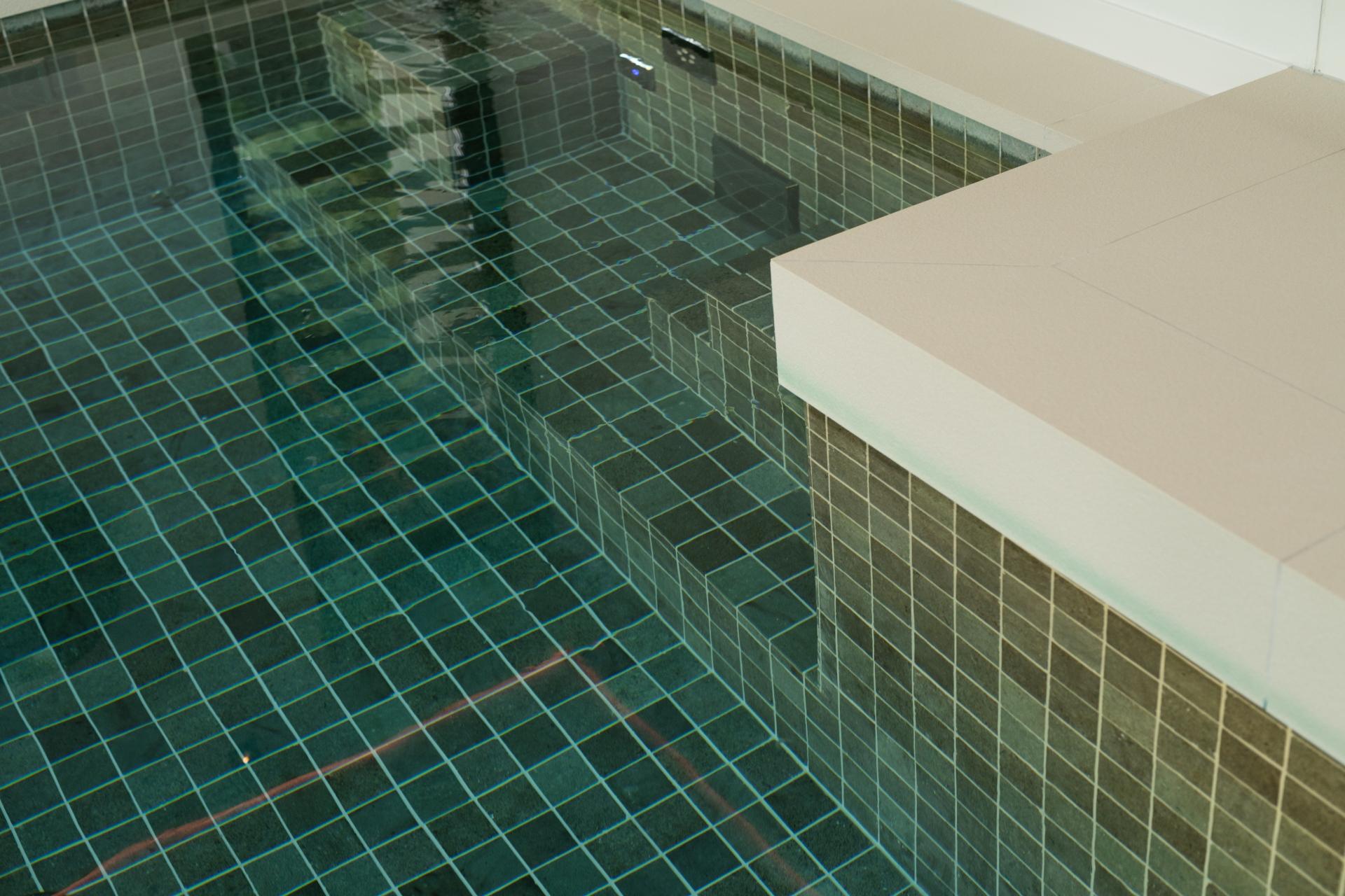 Bouwkundig zwembad met kleine tegels in de kleur groen blauw