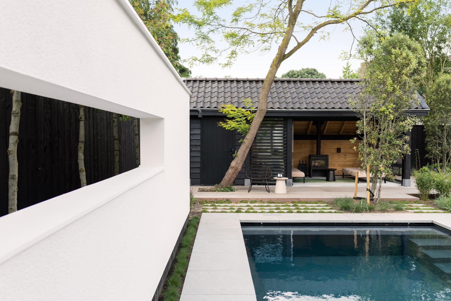 Donkergrijs inbouwzwembad met poolhouse en grijze tegels in moderne tuin