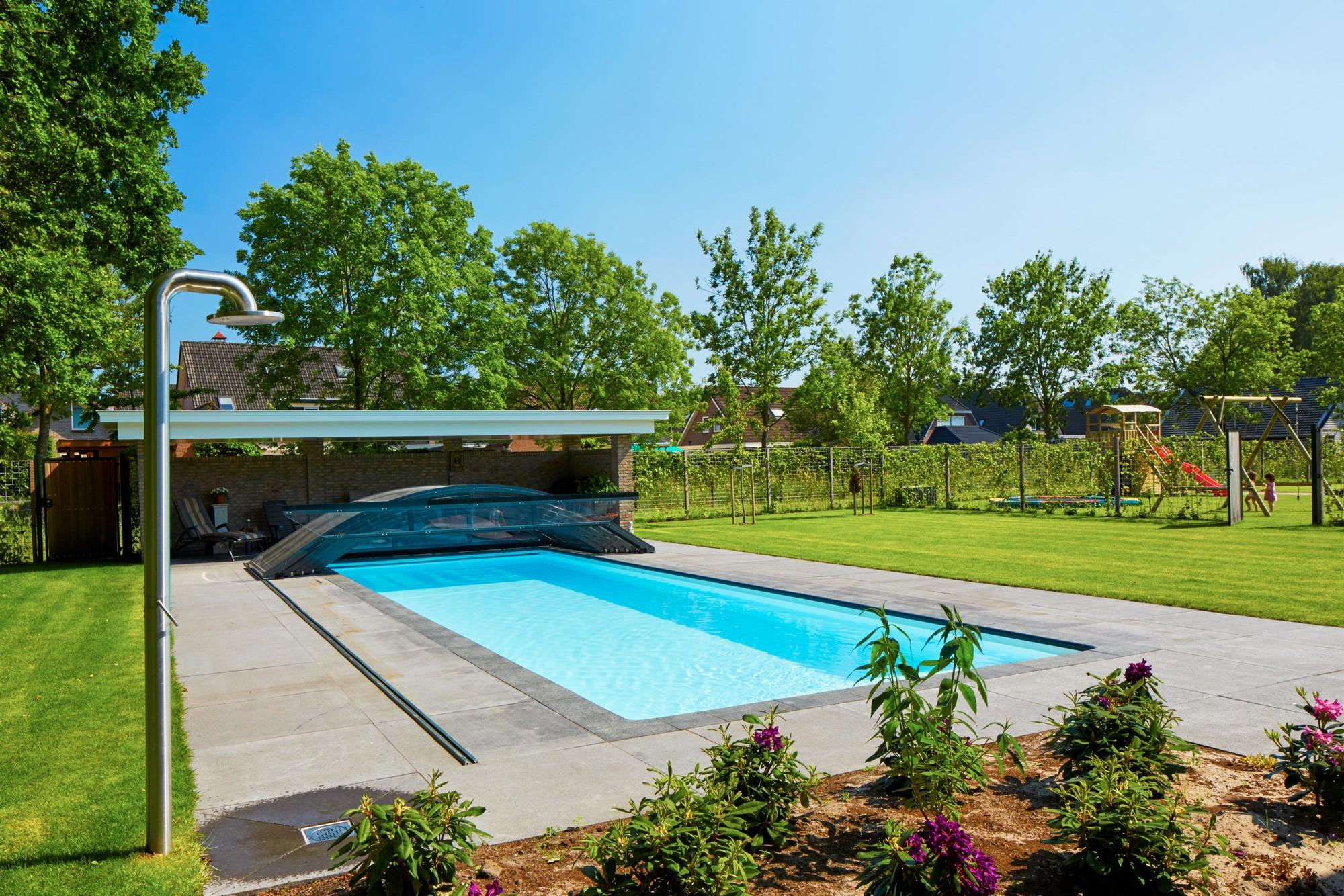 Zwembad met een zwembadoverkapping en buitendouche